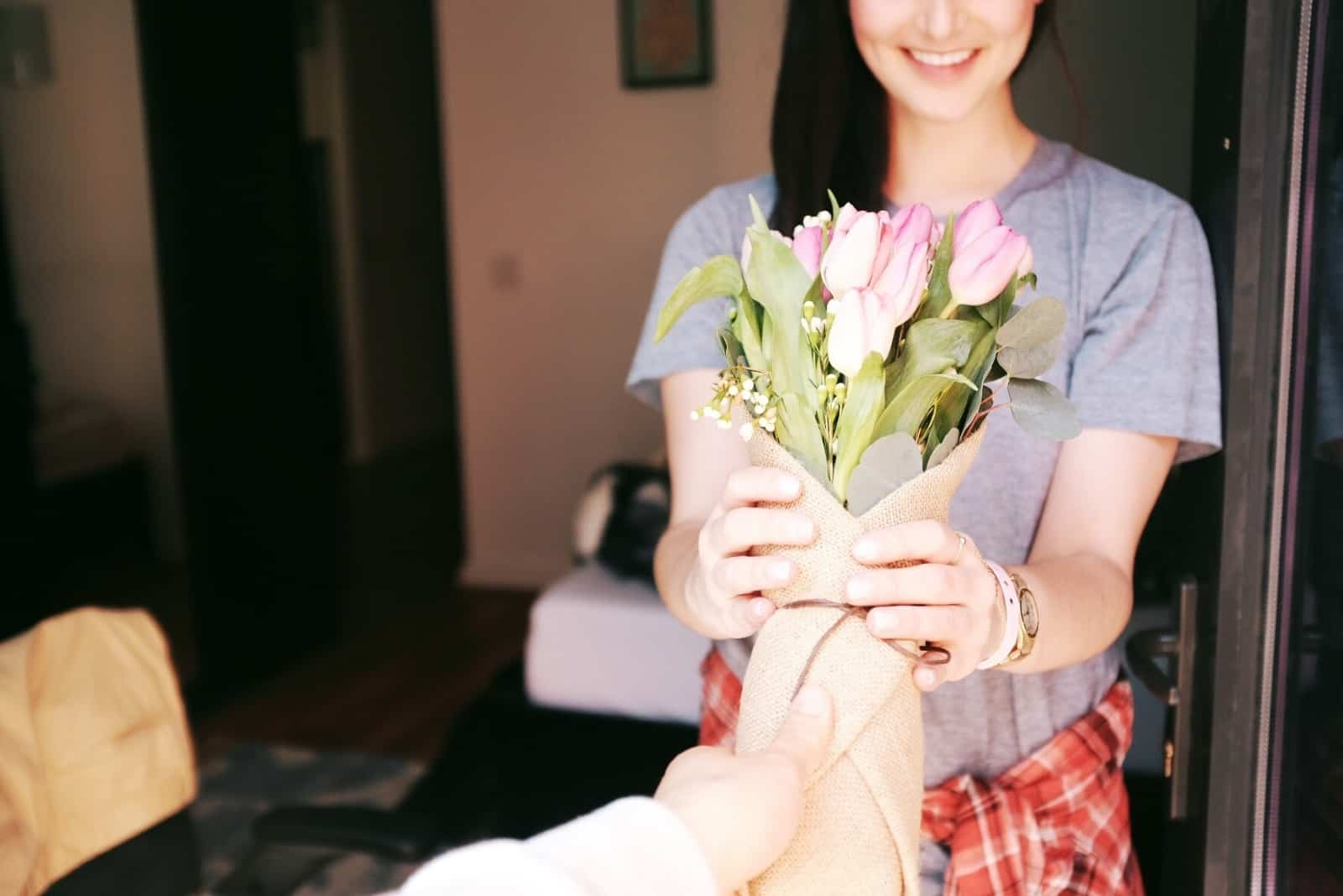man giving bouquet of flowers to woman in gray t-shirt