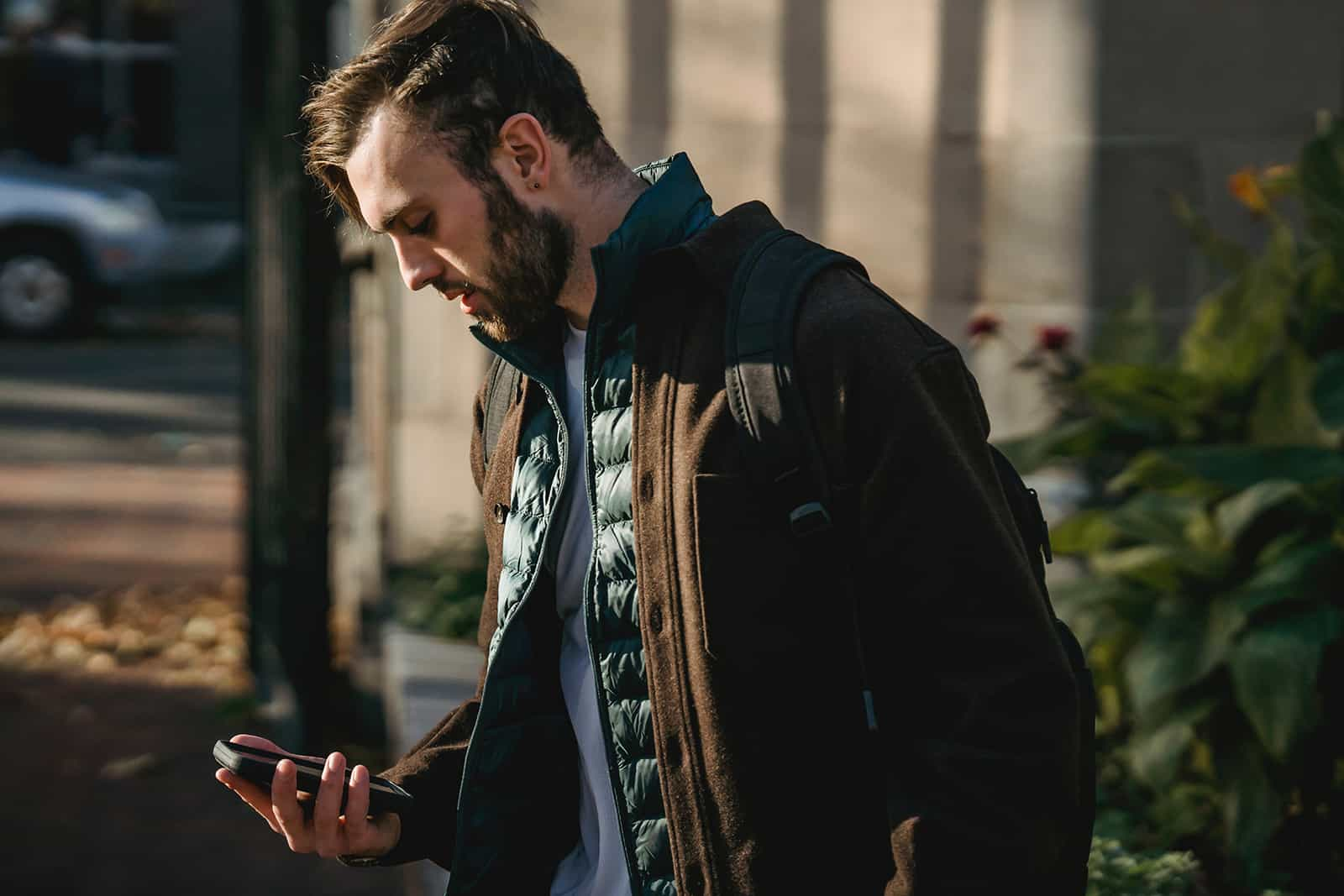 man looking at smartphone while standing outdoor alone