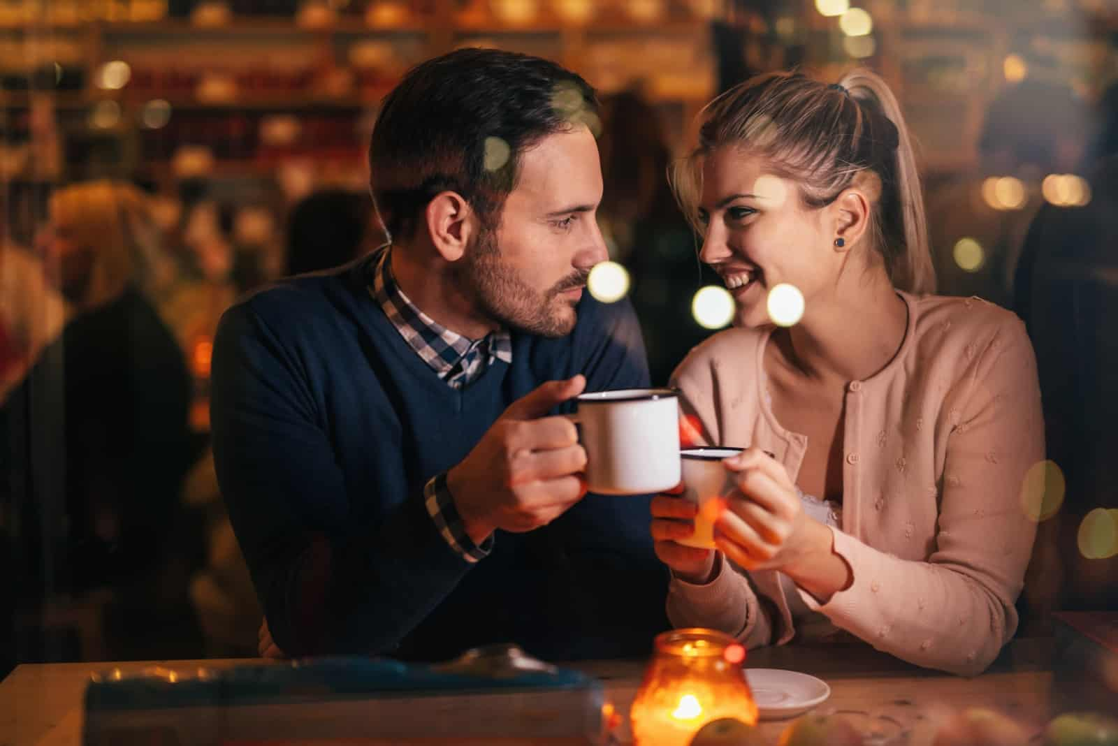man looking at woman while sitting in cafe