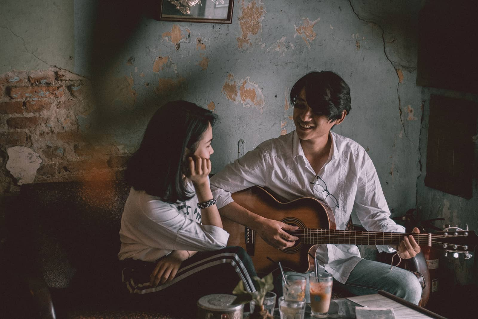 man playing guitar to a smiling woman while sitting together on the couch