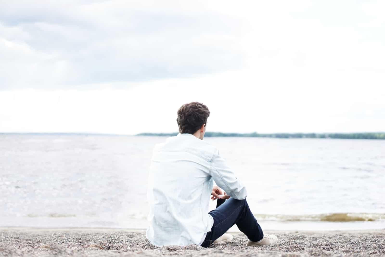 man in white shirt sitting near water