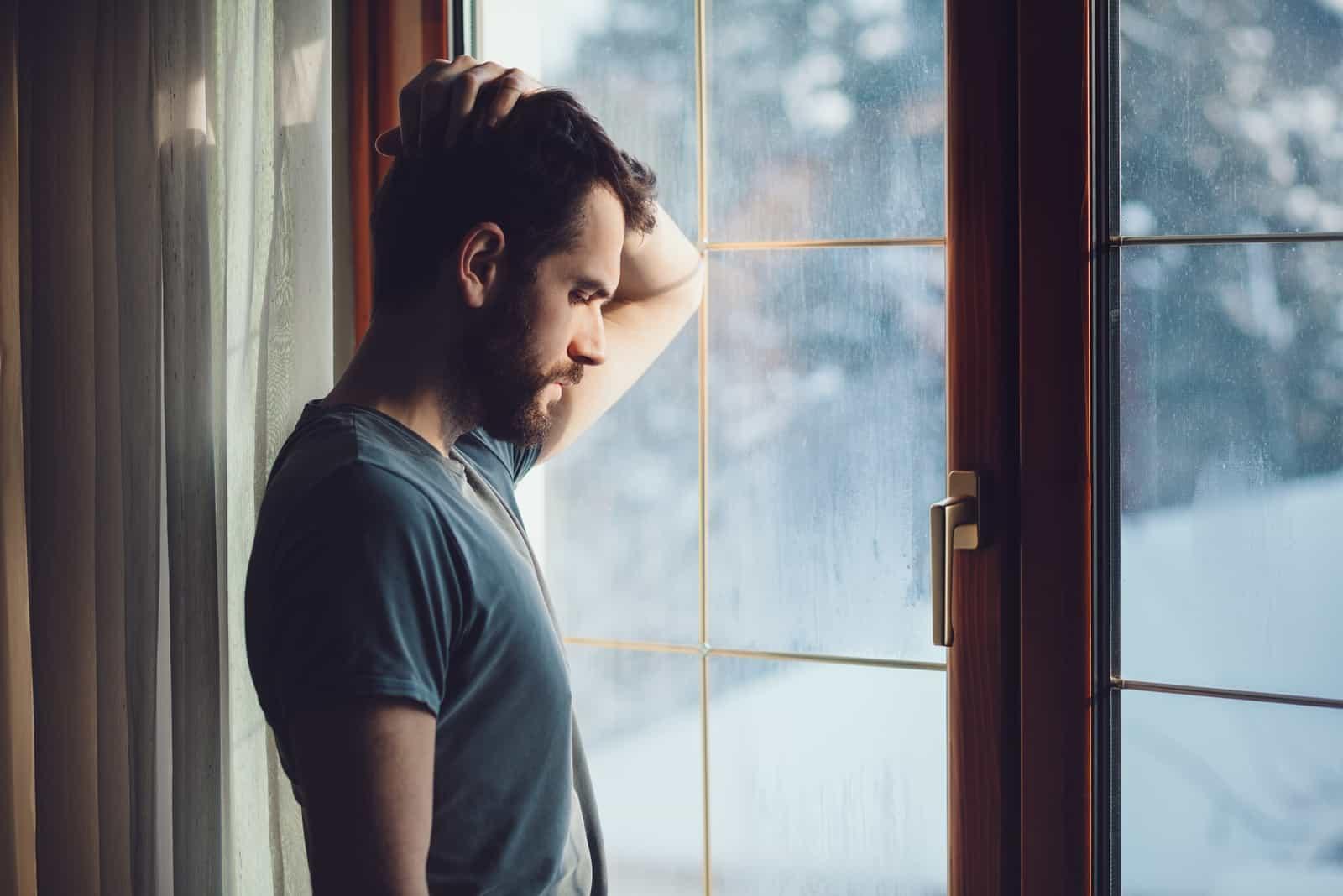 sad man standing near window during daytime