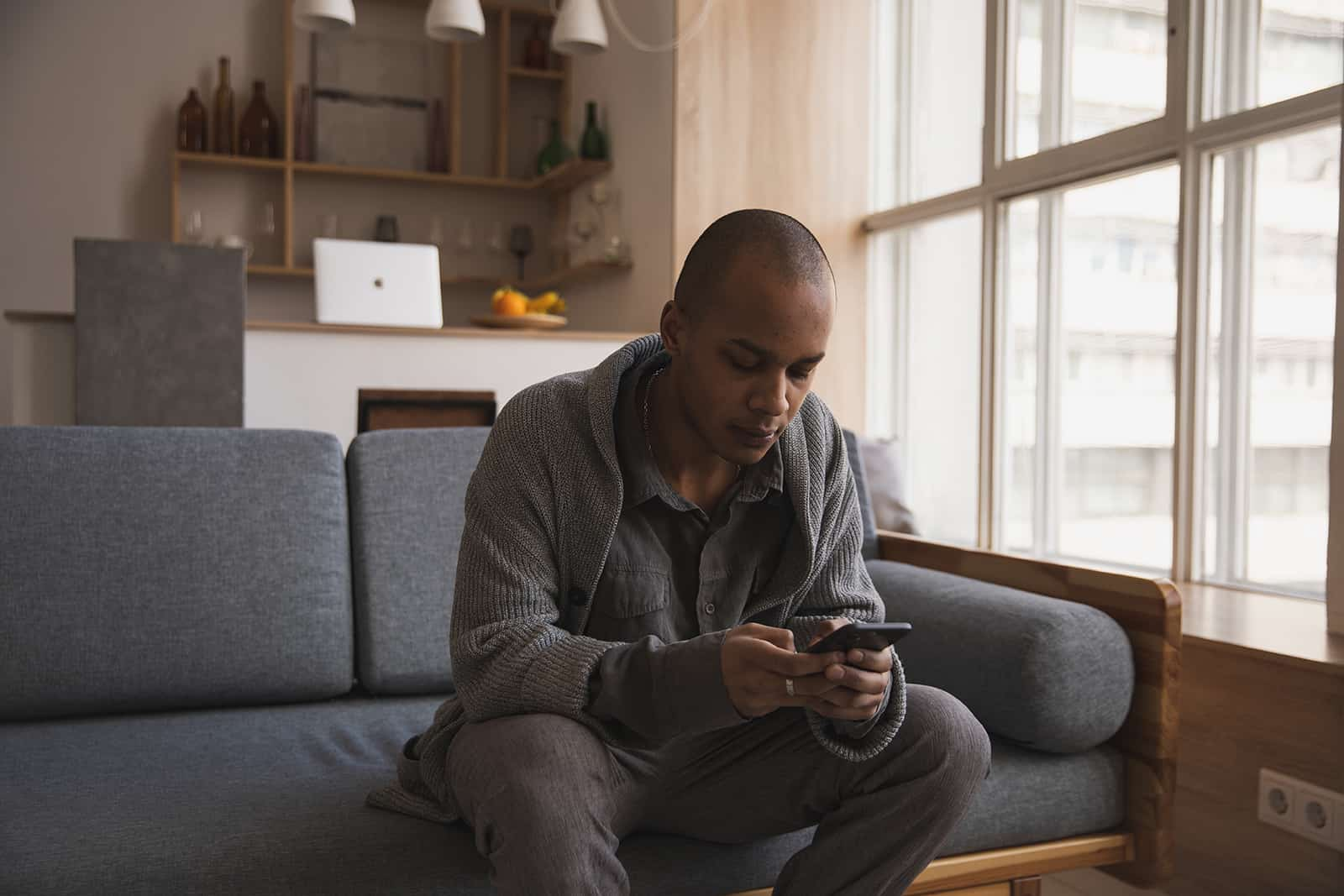 man typing on his smartphone while sitting on the couch at home
