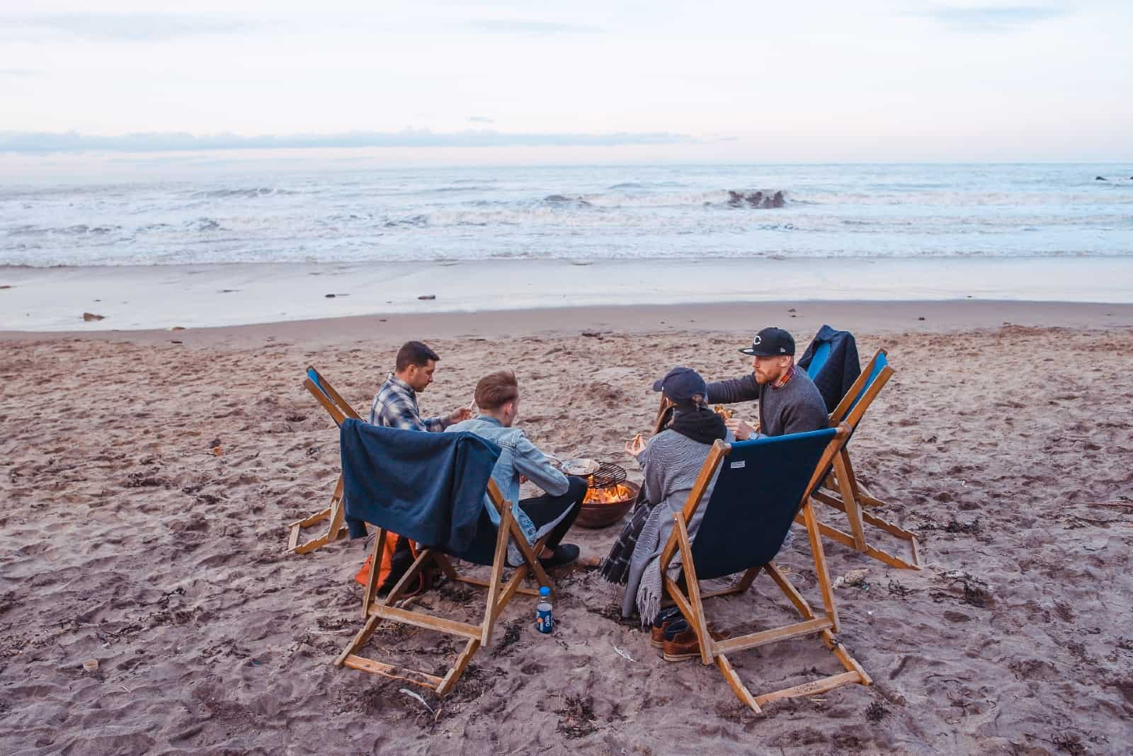 four people sitting on beach near fire pit