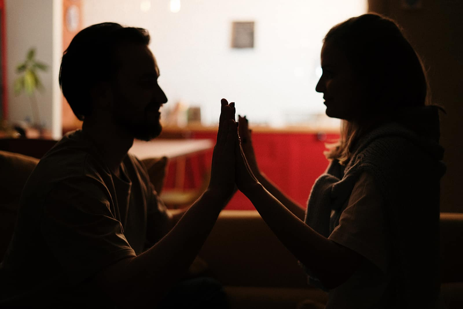 romantic couple holding hands and looking at each other in the dark