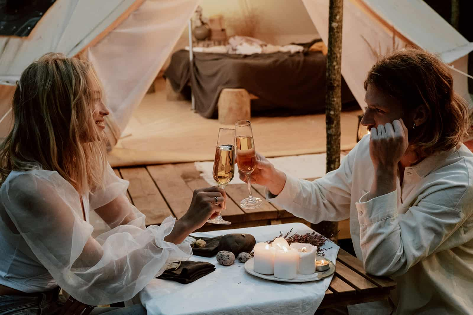 romantic couple toasting with champagne at dinner on the beach