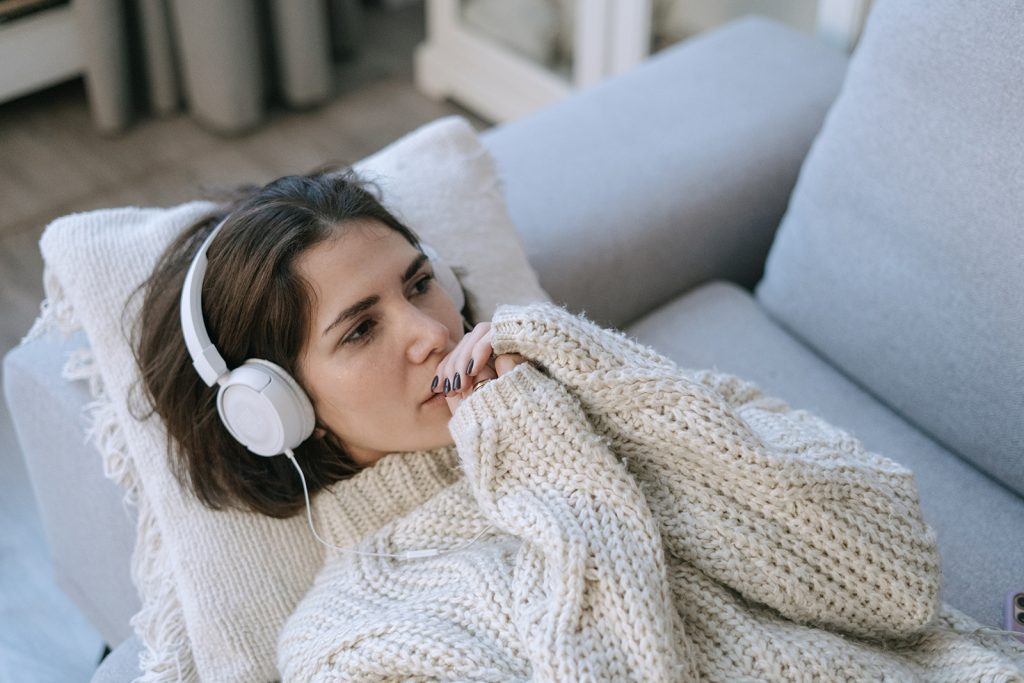 sad woman listening to a music while lying on the sofa