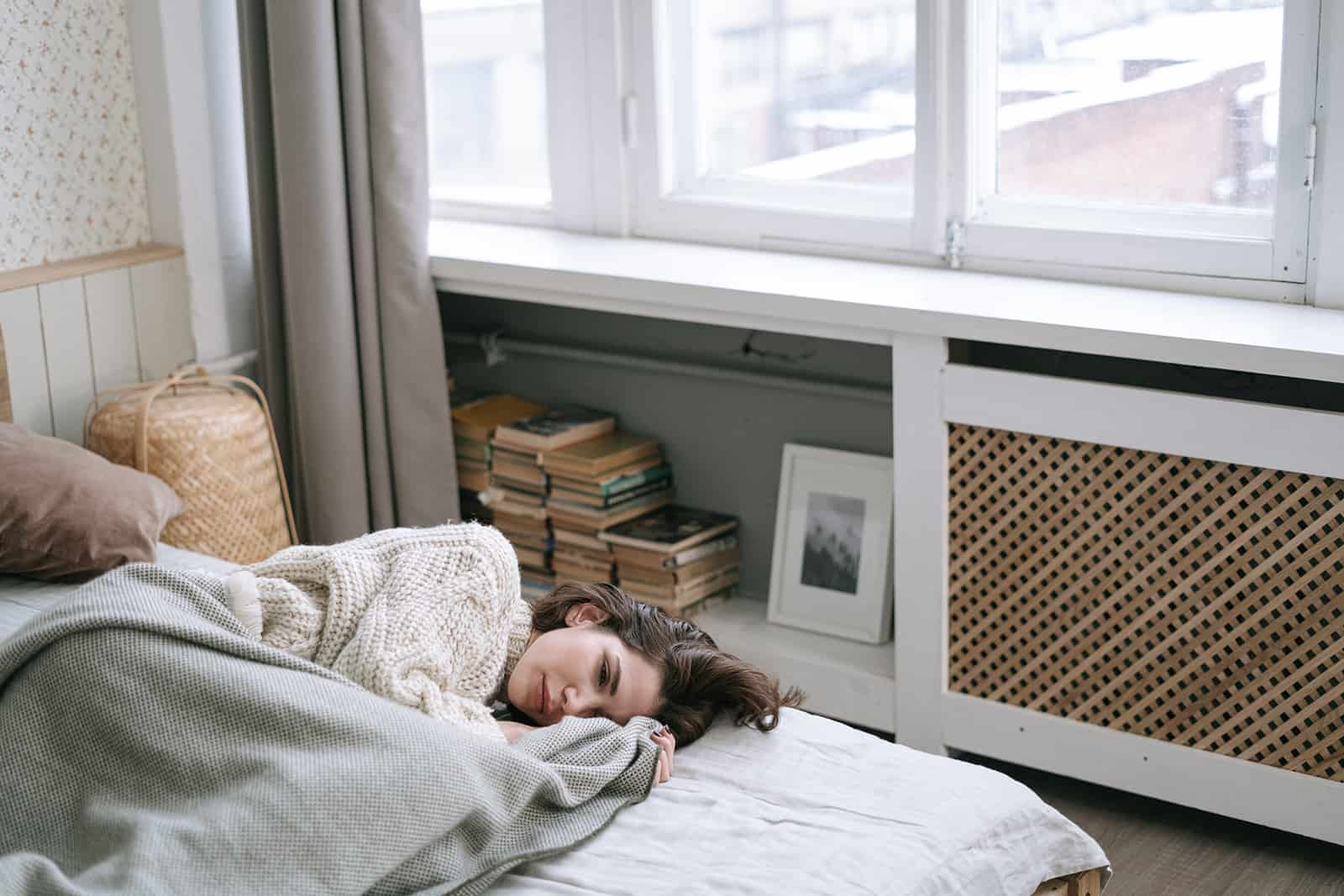 sad woman lying on the bed covered with graY blanket