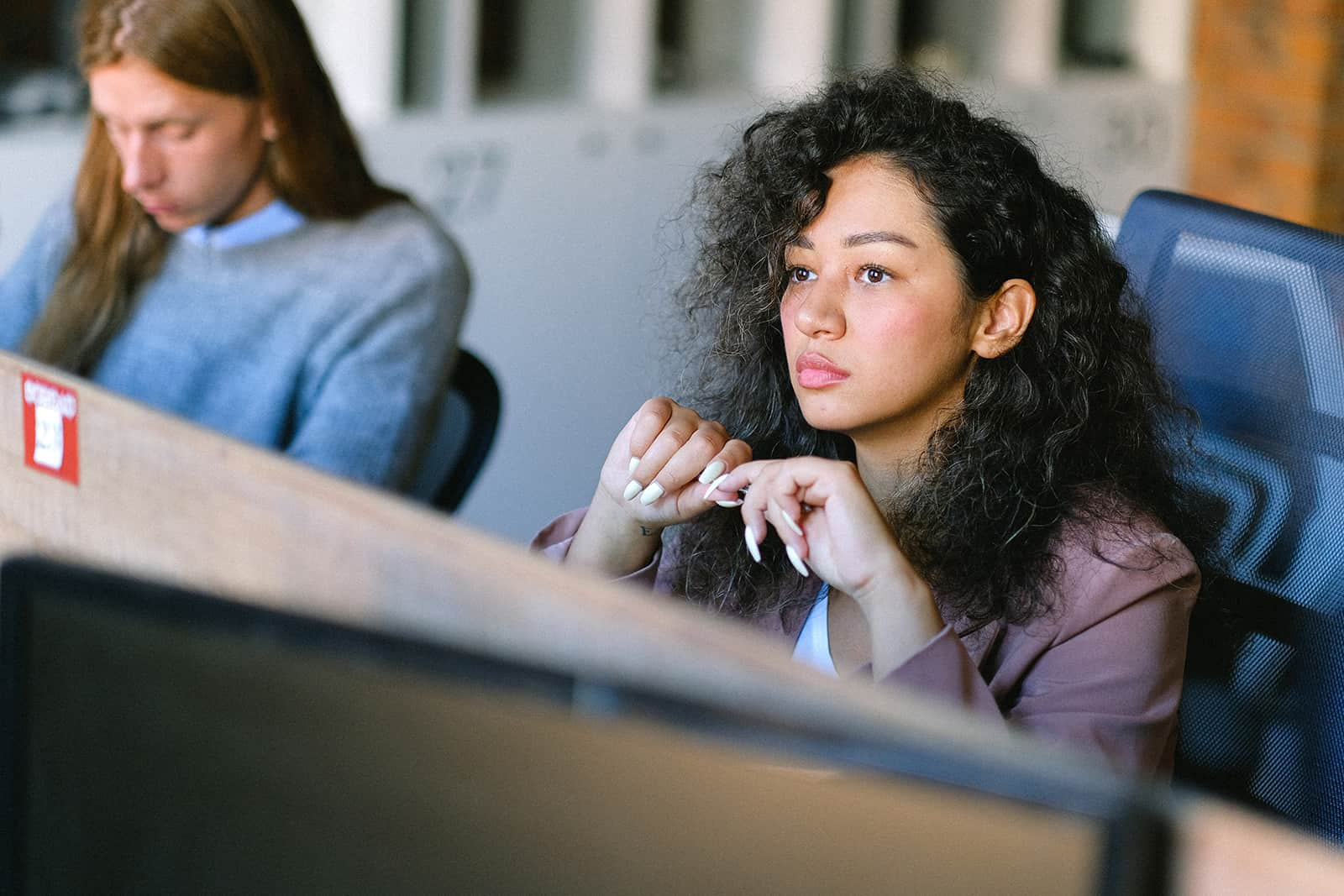 serious woman sitting at workplace and looking in front of her