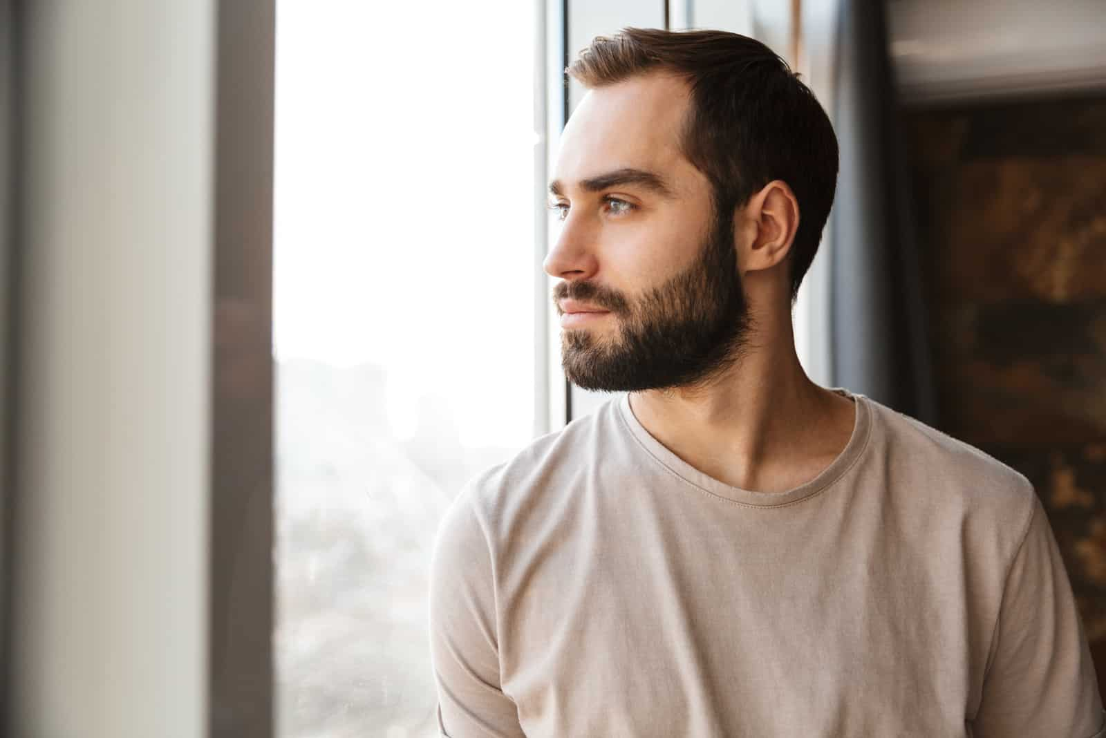 serious young bearded man standing at the window at home
