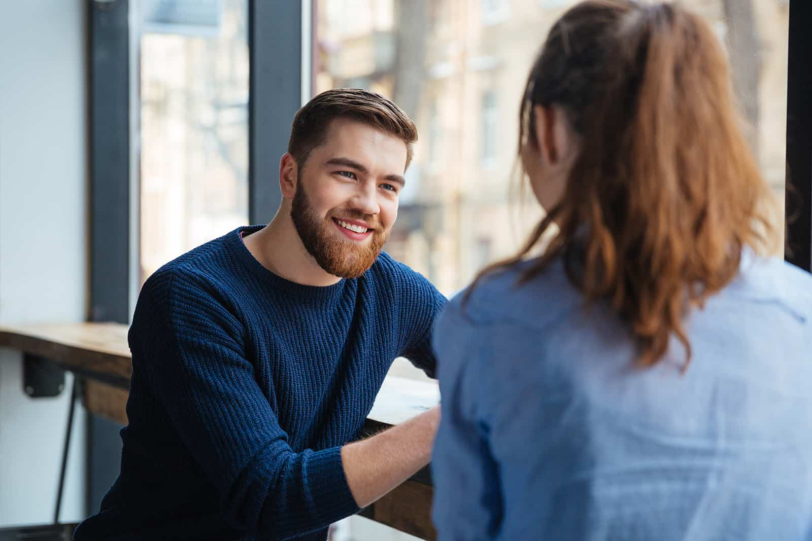 smiling man listening to his girlfriend while sitting in the cafe near the window