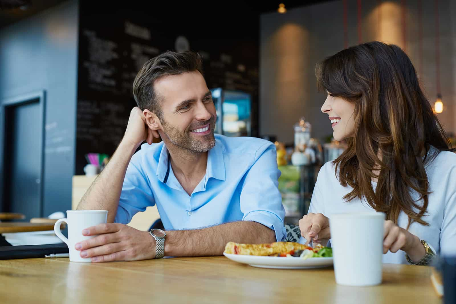 smiling man looking at a woman while having lunch in a cafe