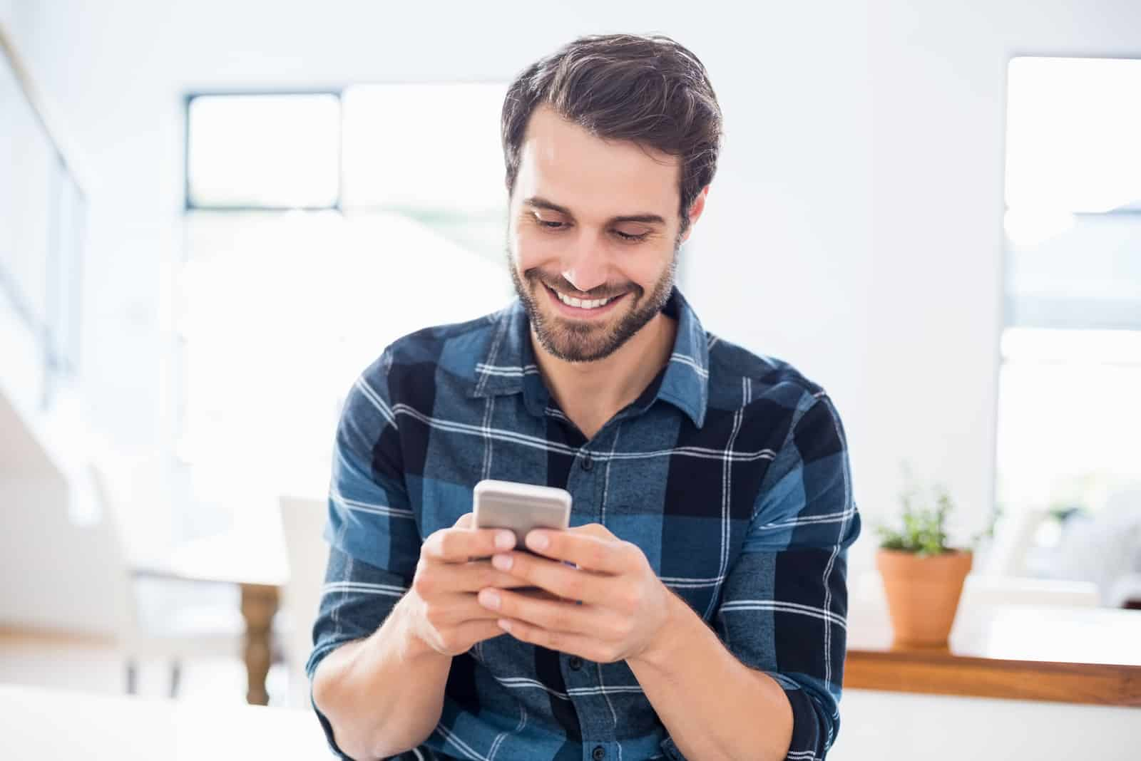 smiling man using his phone