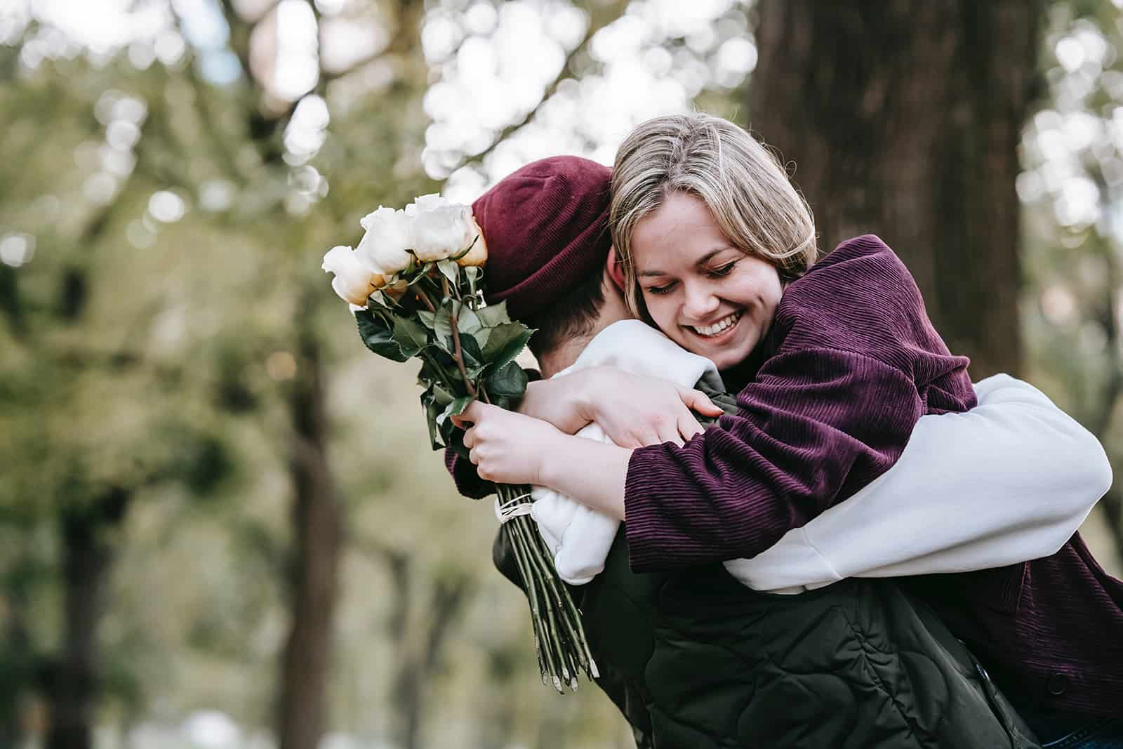 smiling woman hugging her boyfriend while holding white roses
