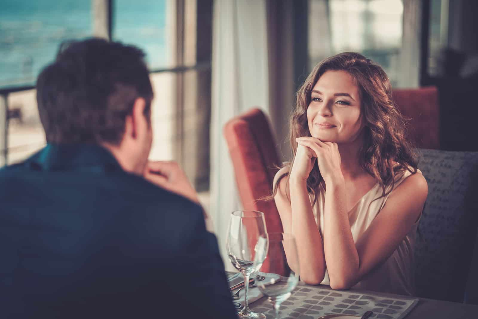 smiling woman looking at a man while sitting together in a restaurant