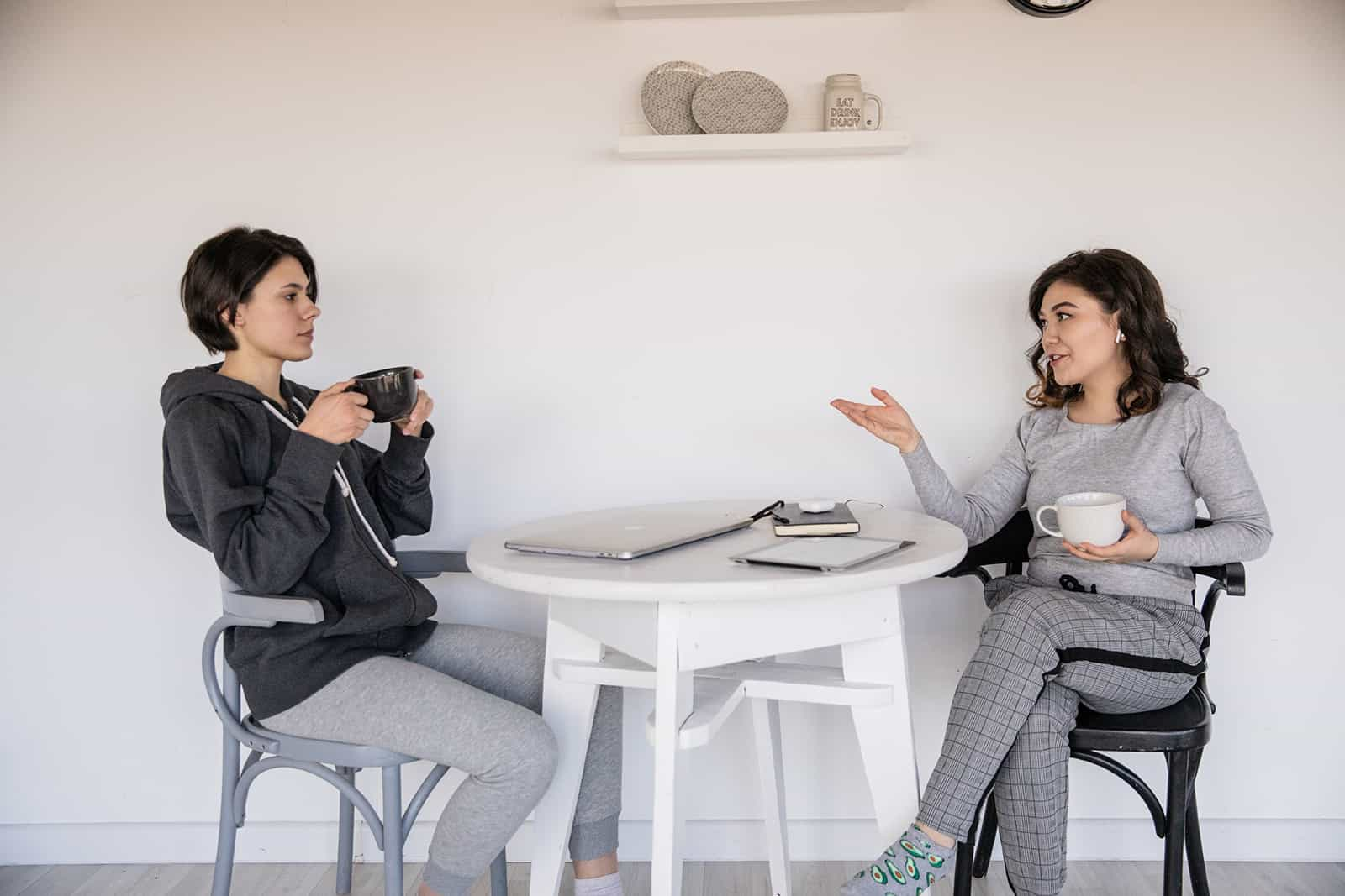 two female friends having serious conversation while sitting at the table at home