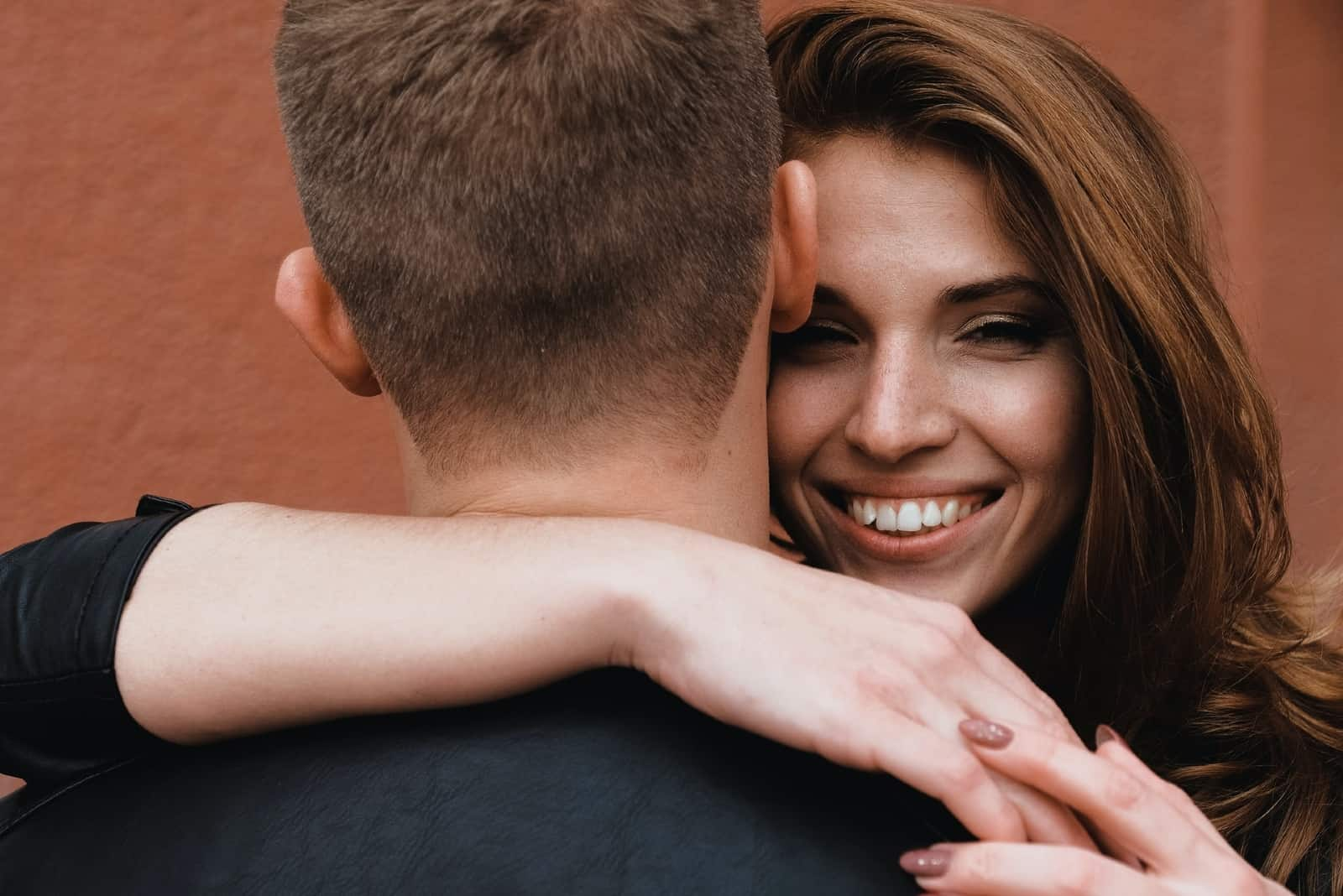 happy woman hugging man while standing near wall