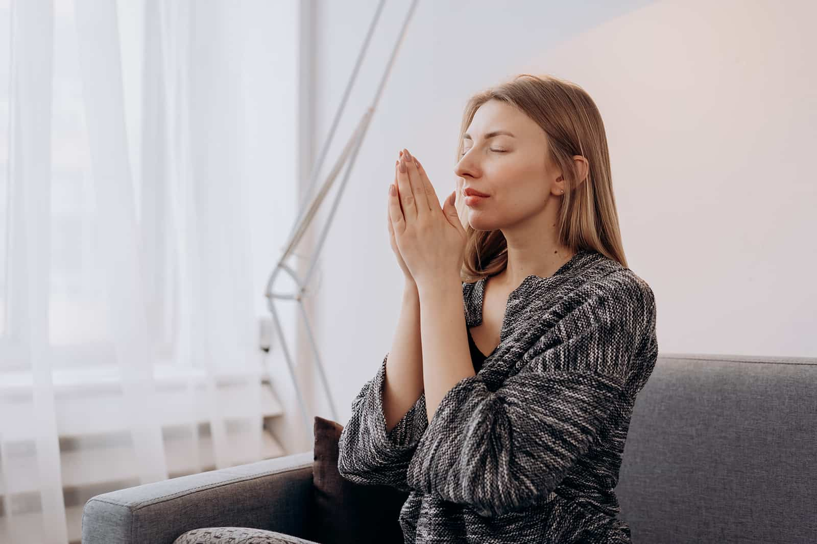 woman praying with eyes closed while sitting on couch