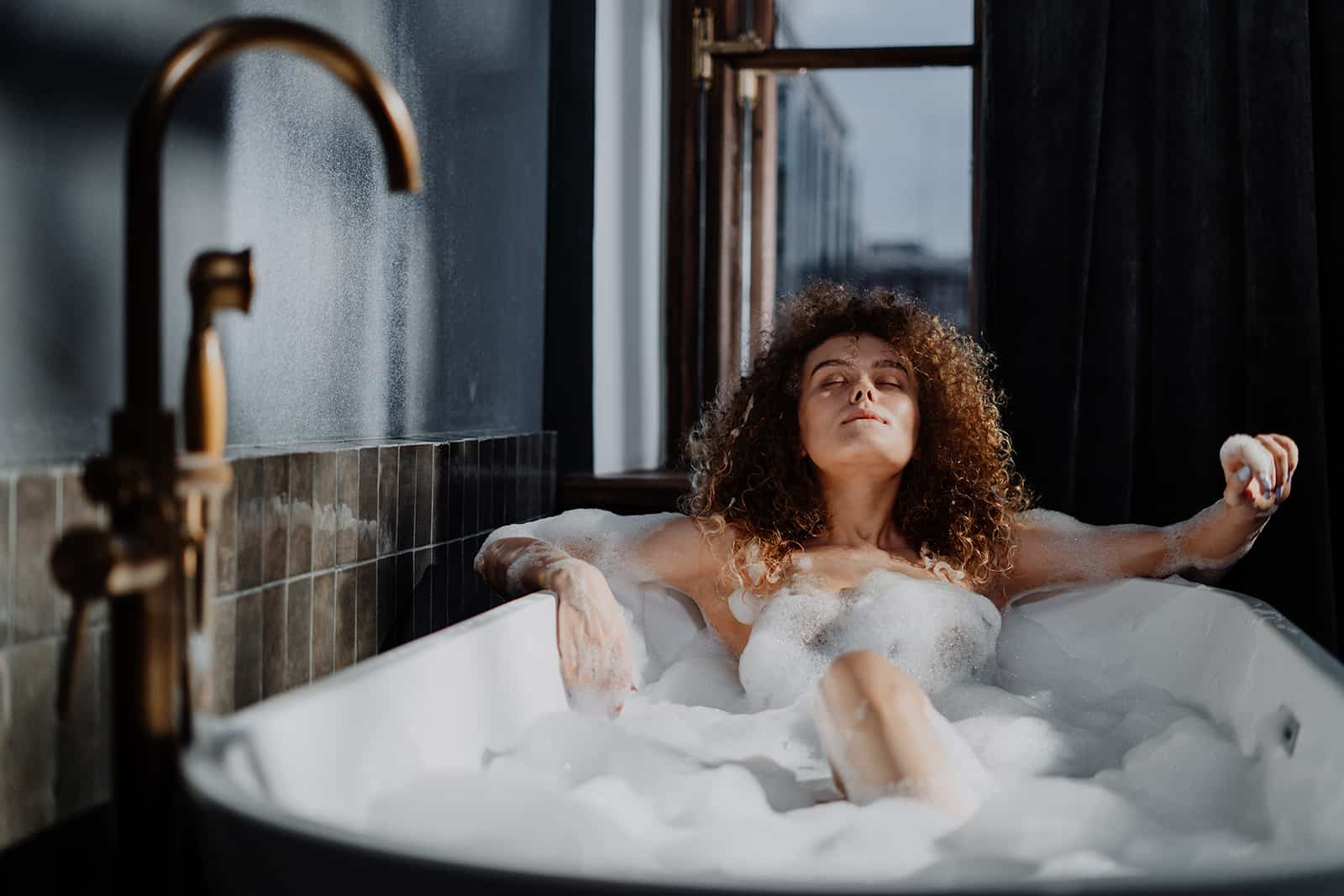 woman relaxing in a bathtub with eyes closed