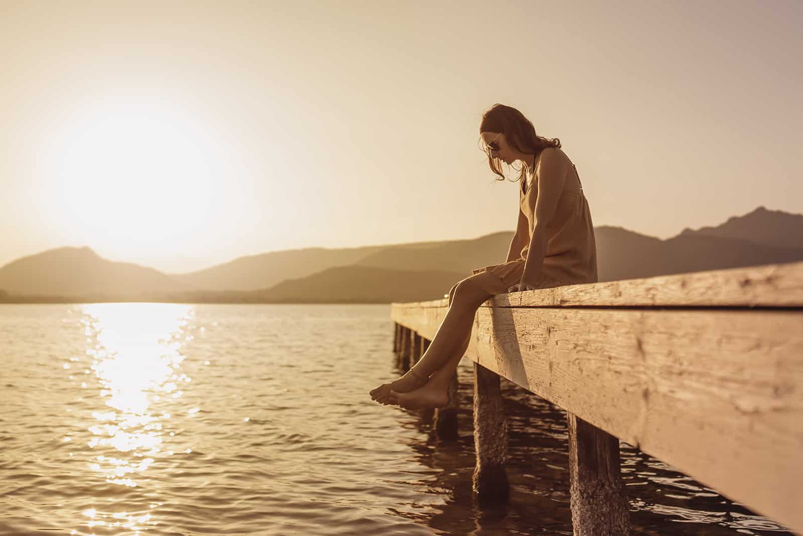 woman sitting alone on a pier of a lake and looking down