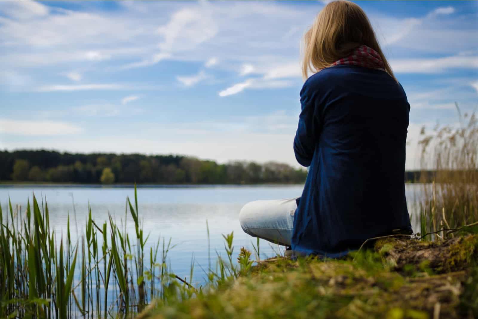 woman in blue cardigan sitting near lake