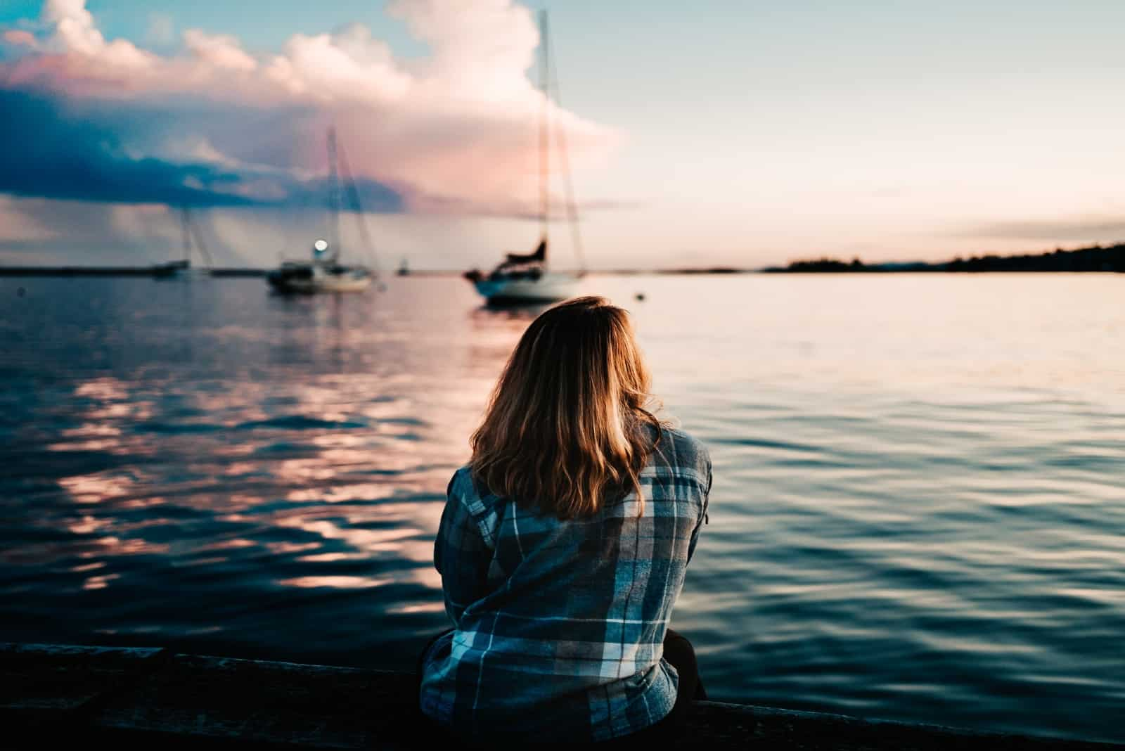 woman in blue checked shirt sitting near sea