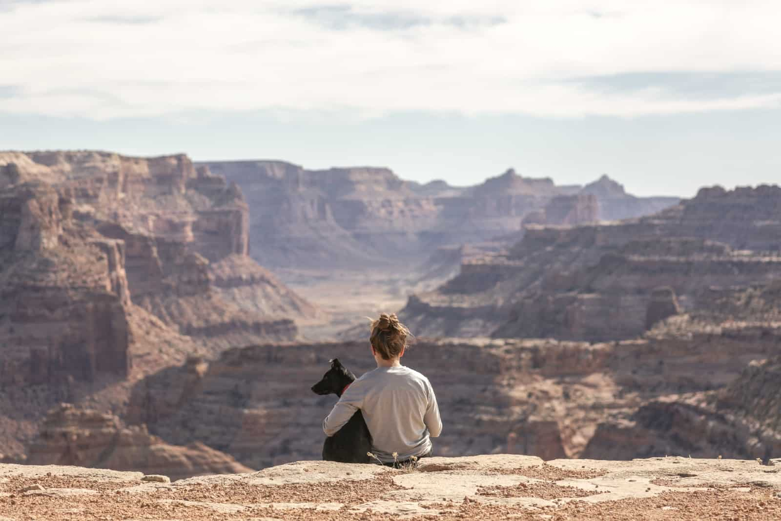 woman hugging black dog while sitting on cliff