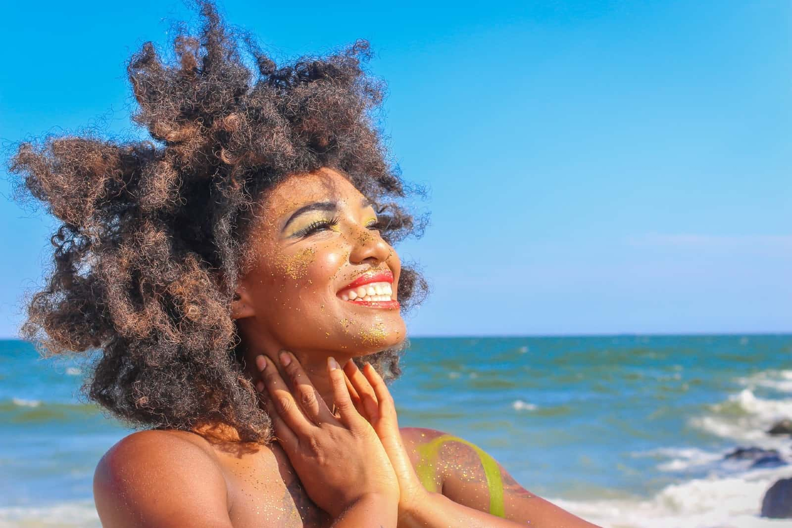woman with curly hair smiling while standing on beach