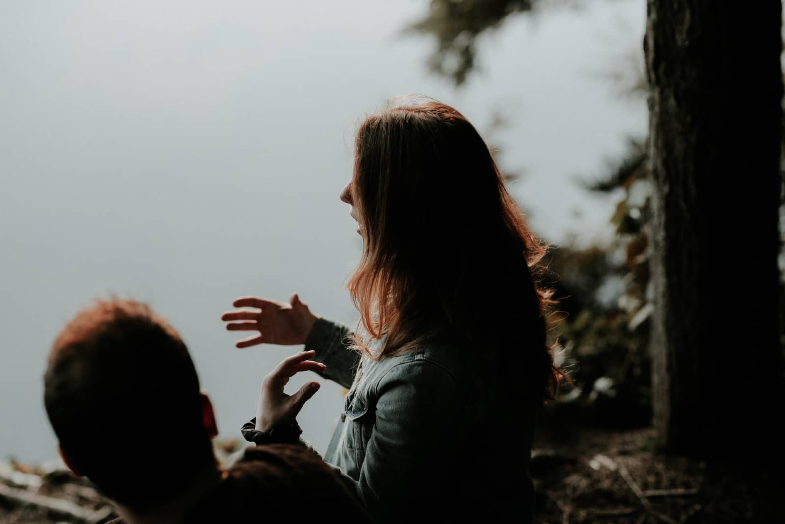 woman talking to man while sitting near water