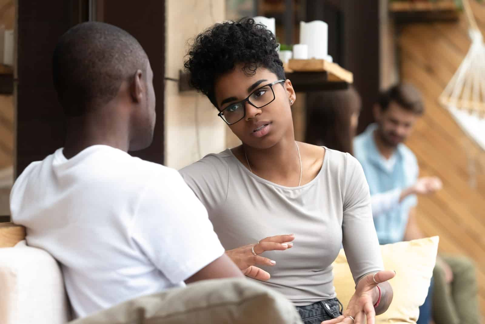 woman with eyeglasses talking to man