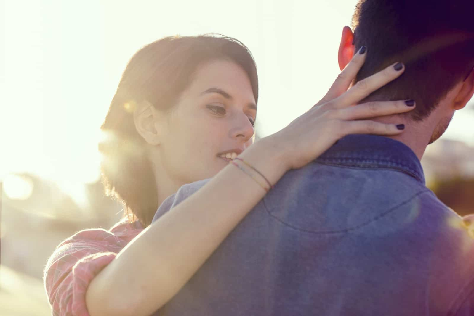 woman touching man's neck while standing outdoor
