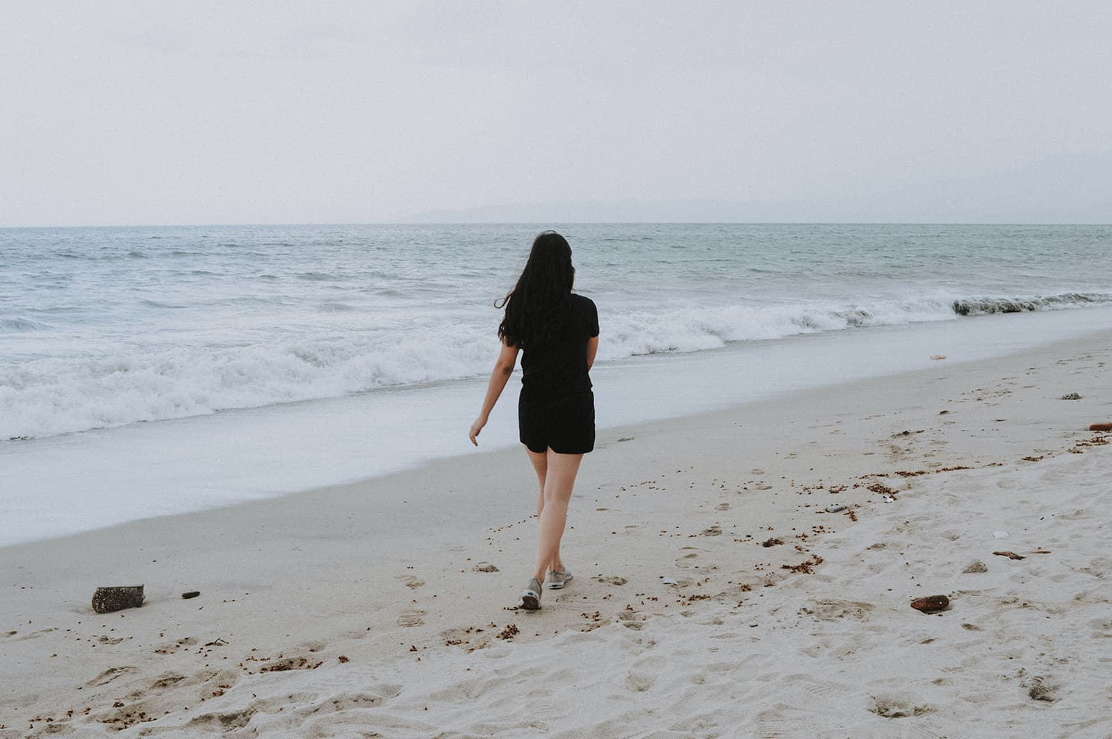 woman walking on the beach alone during daytime