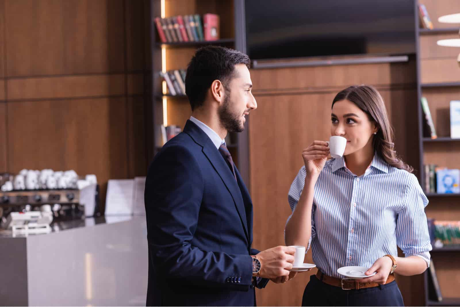 a man and a woman stand drinking coffee and talking
