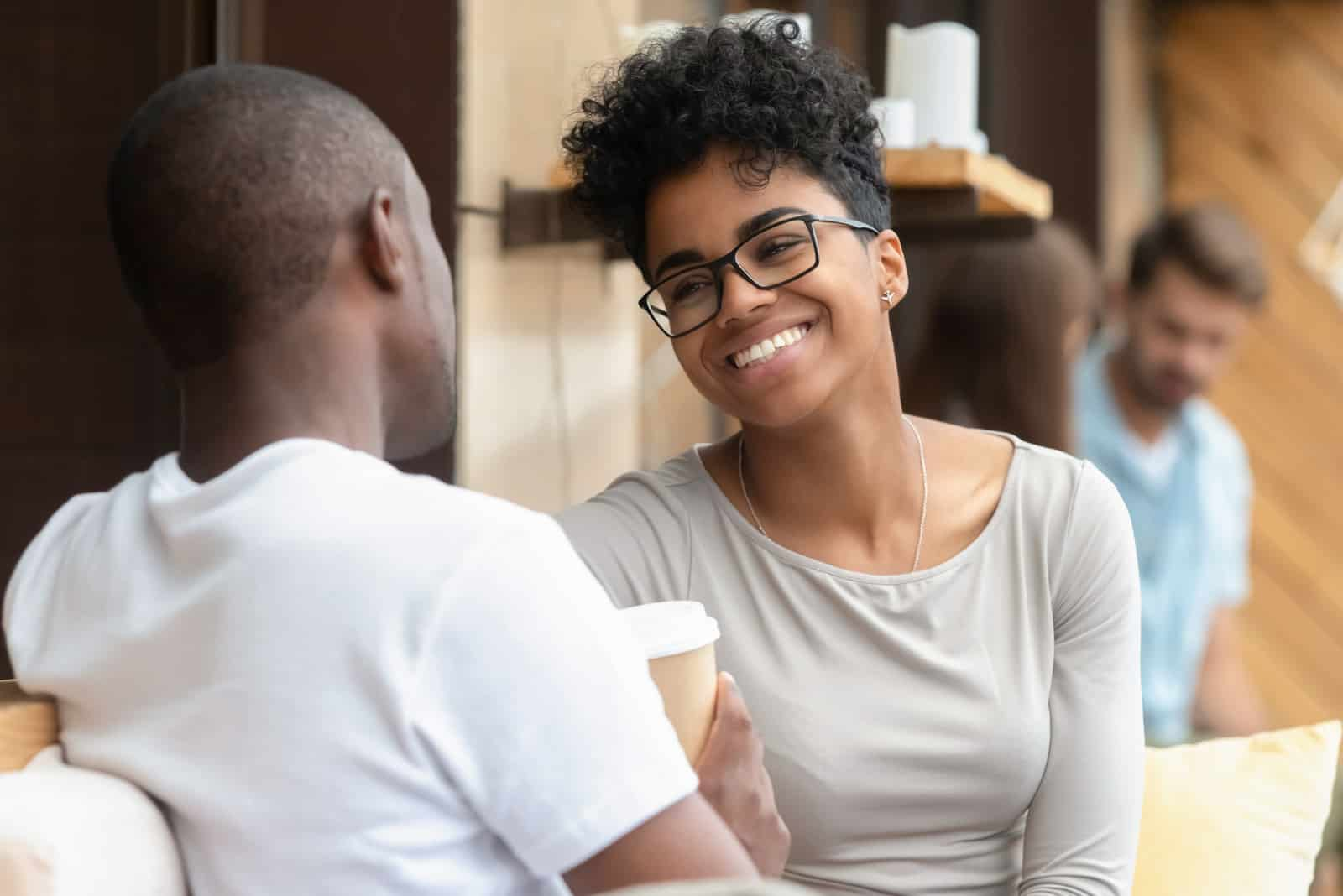 a smiling couple sitting drinking coffee and talking