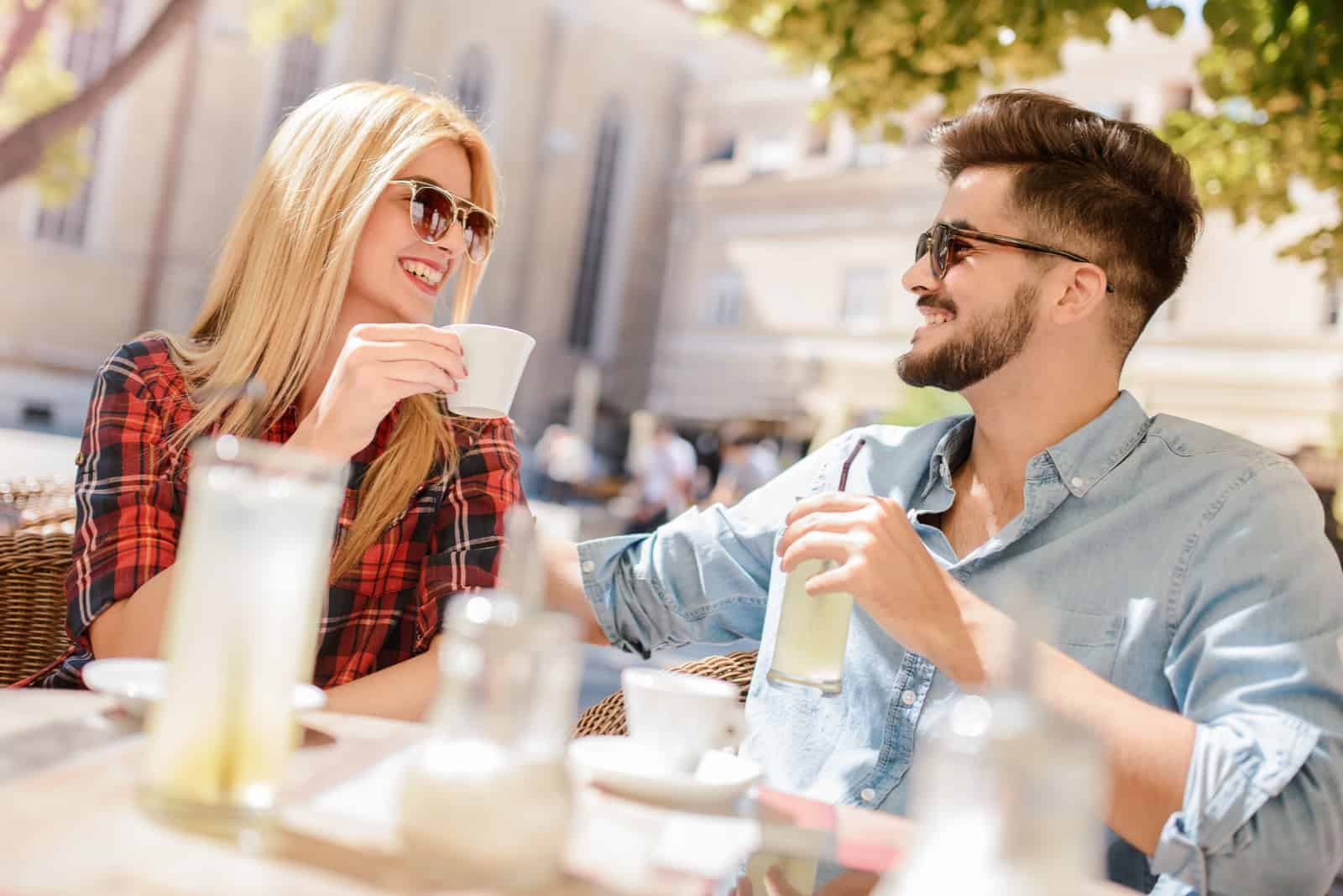 a smiling man and woman sit outdoors and talk over coffee