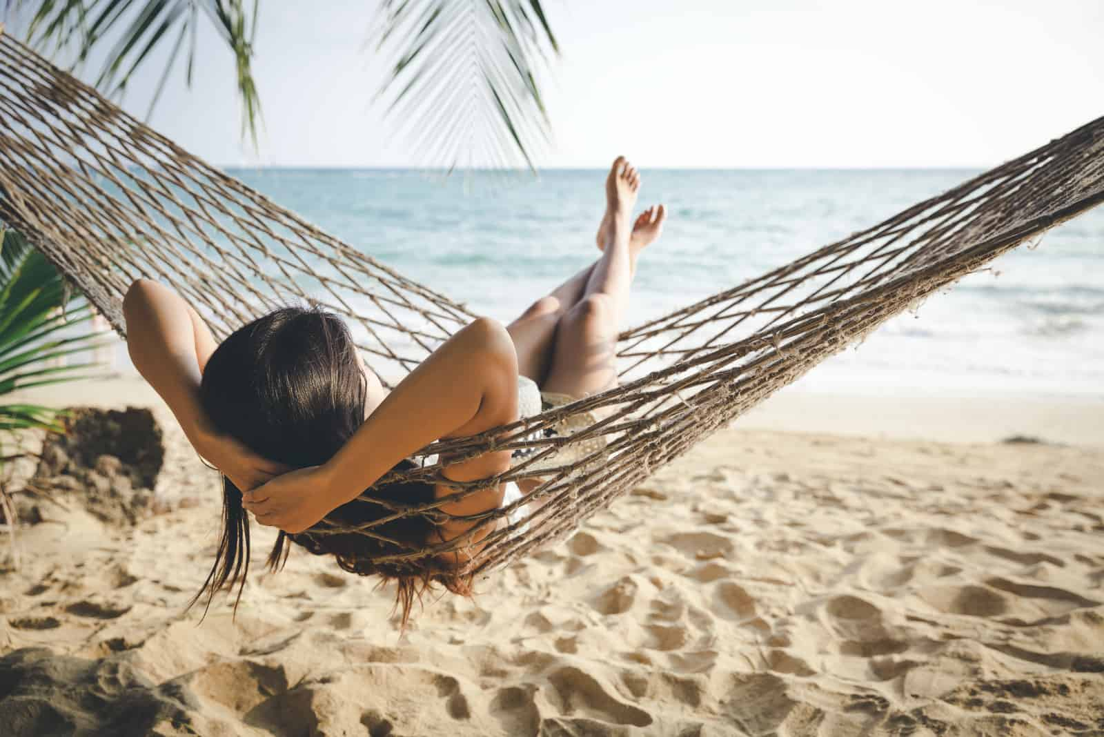 the woman is lying on a deck chair