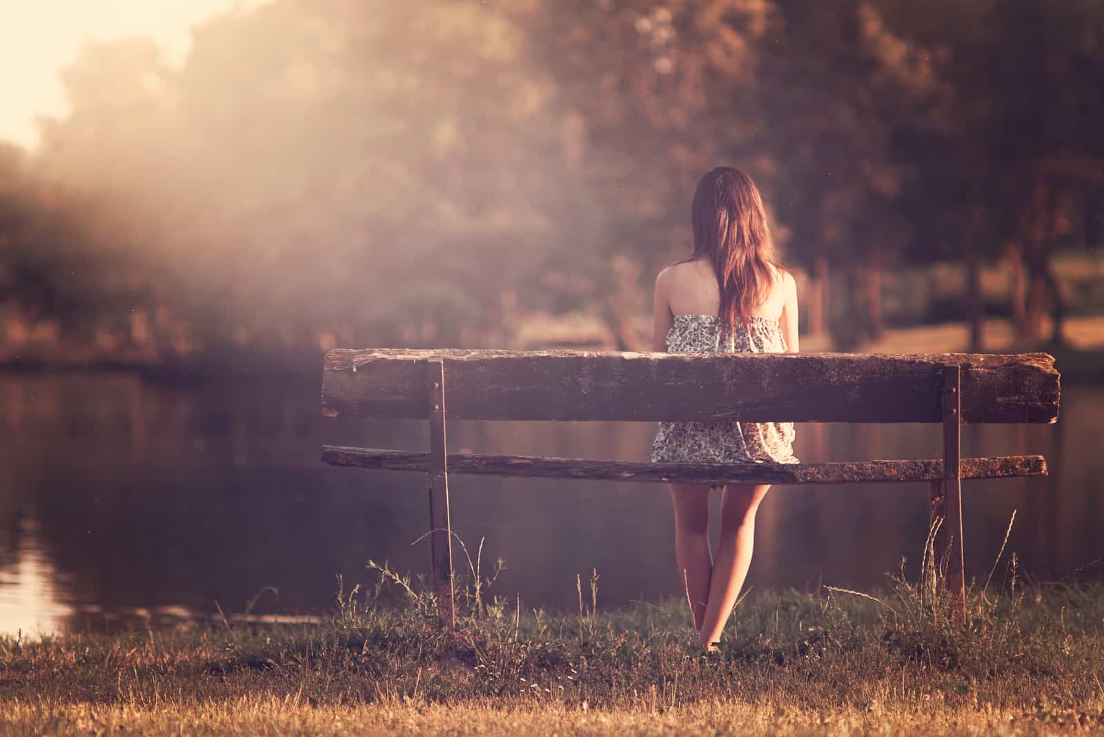 the woman sits on a bench and looks out at the lake