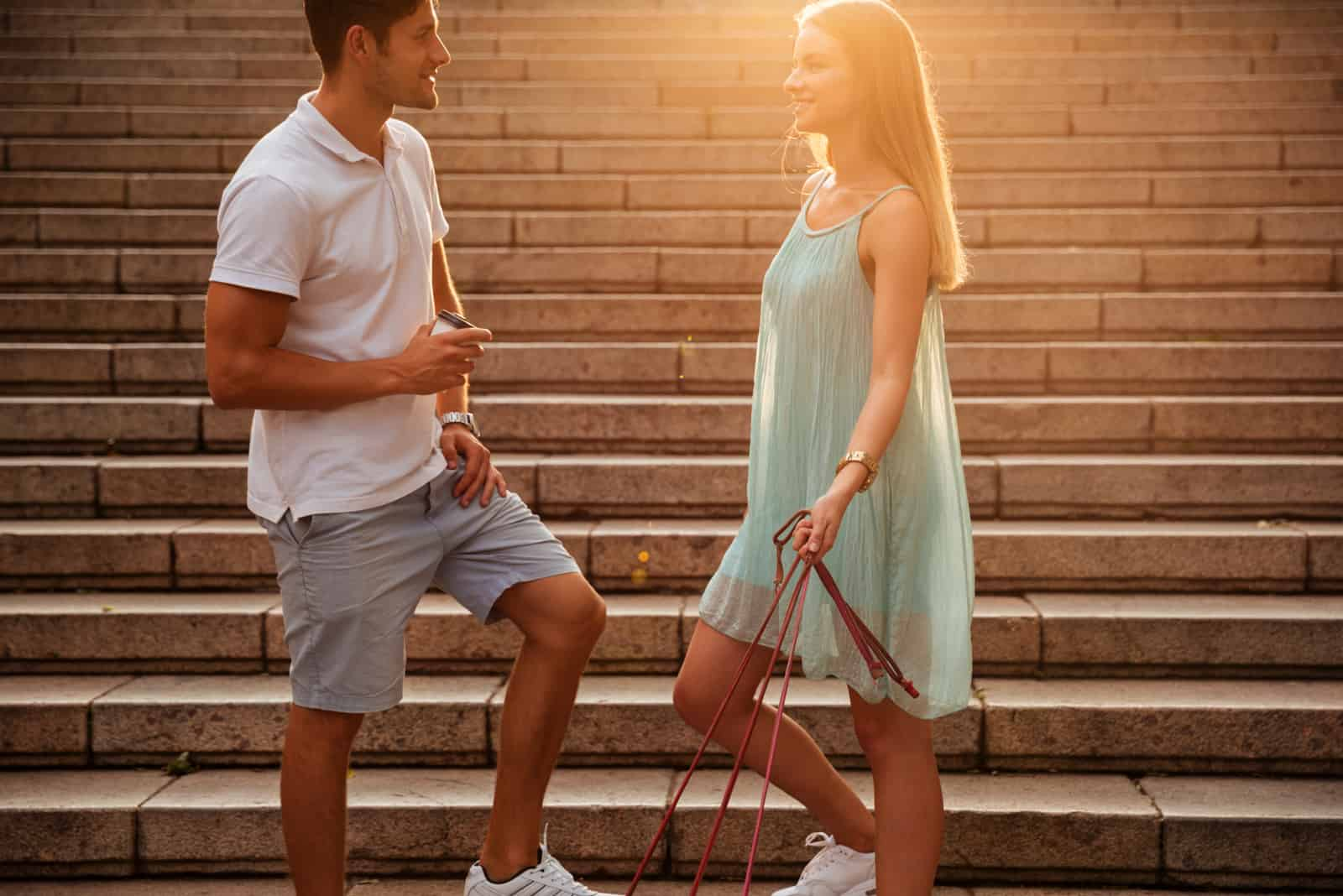 a smiling man and woman stand on the stairs and talk