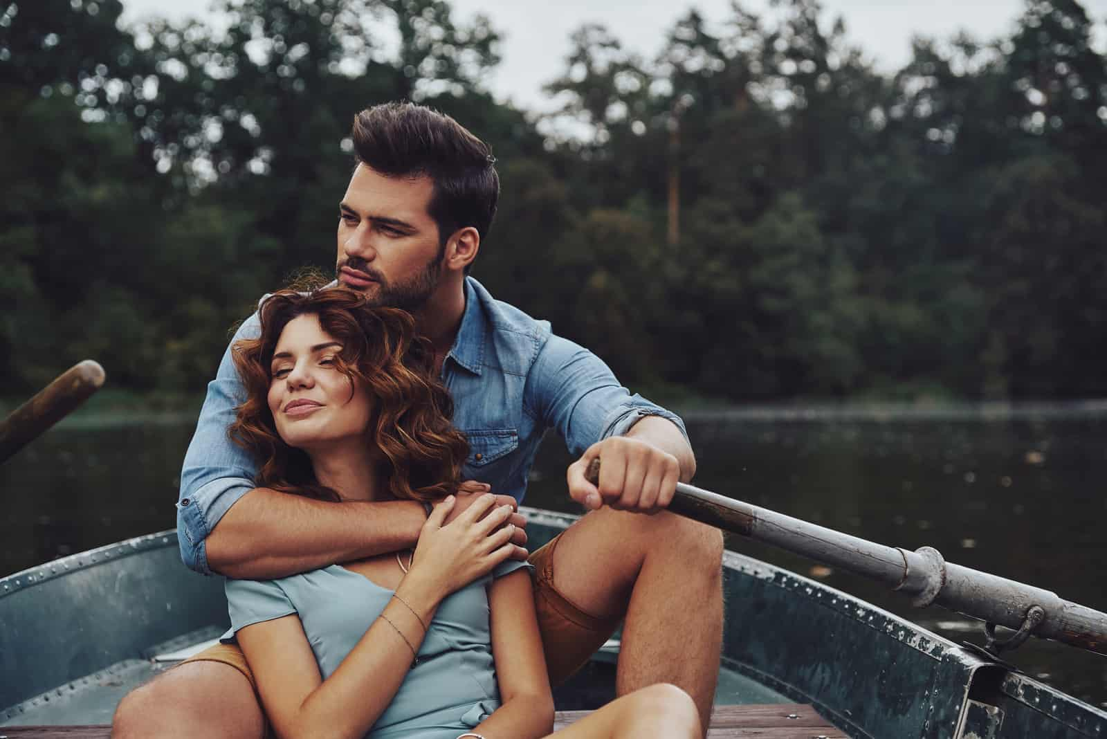 the man hugged the woman as they sat in the boat