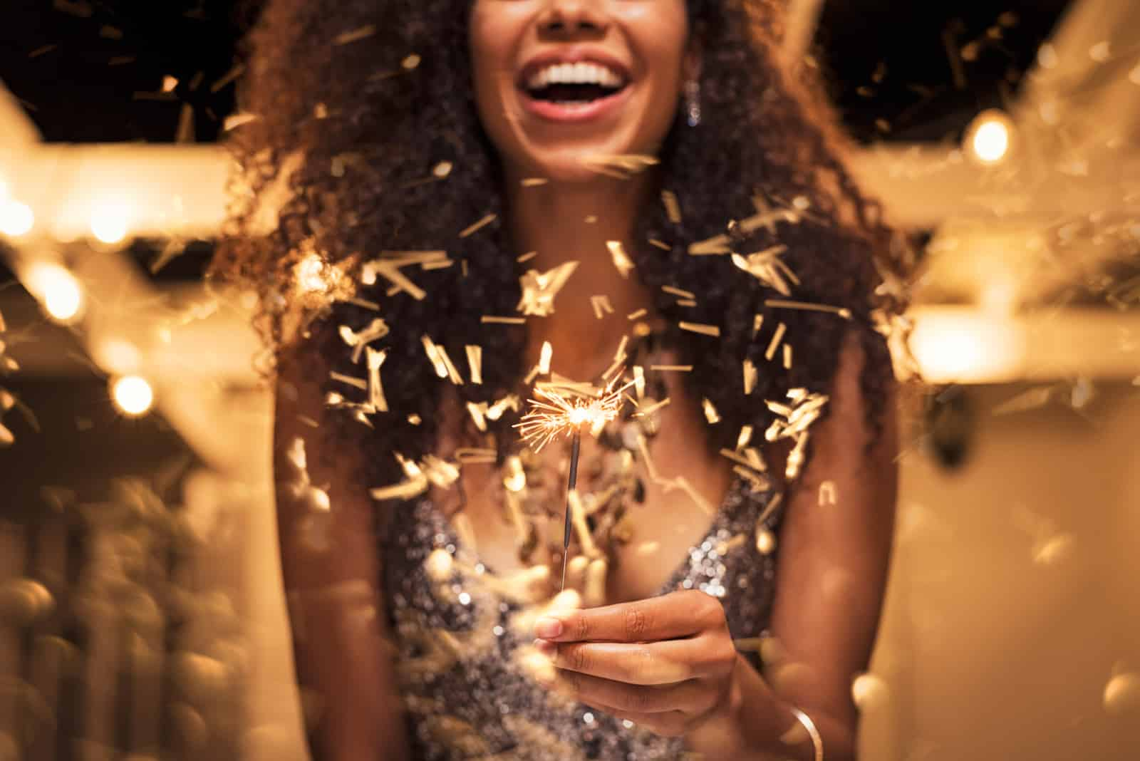Cheerful young woman holding a sparkler