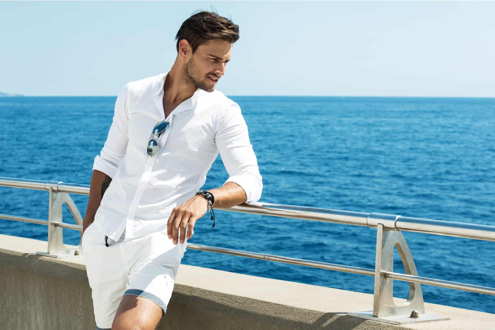 a beautiful man leaning against a fence looks out to sea