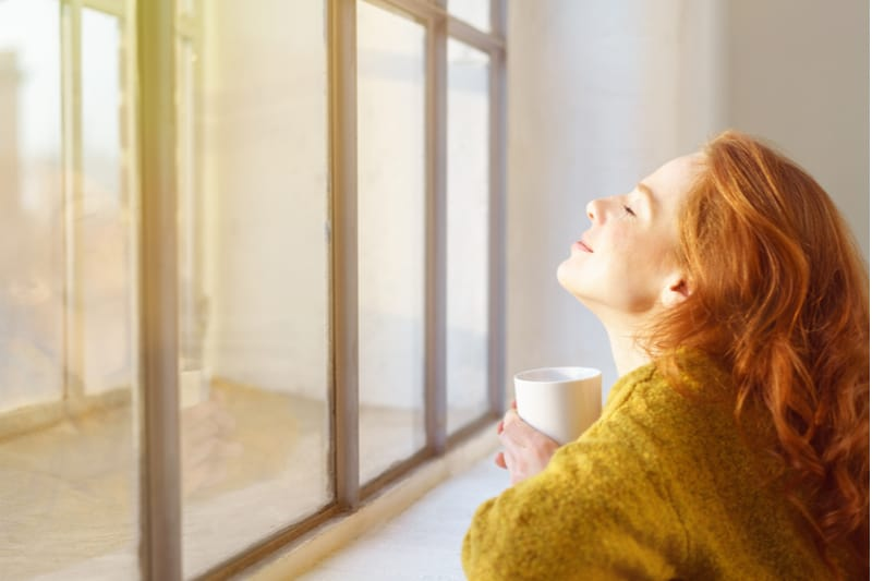 a beautiful woman holding a cup in her hand