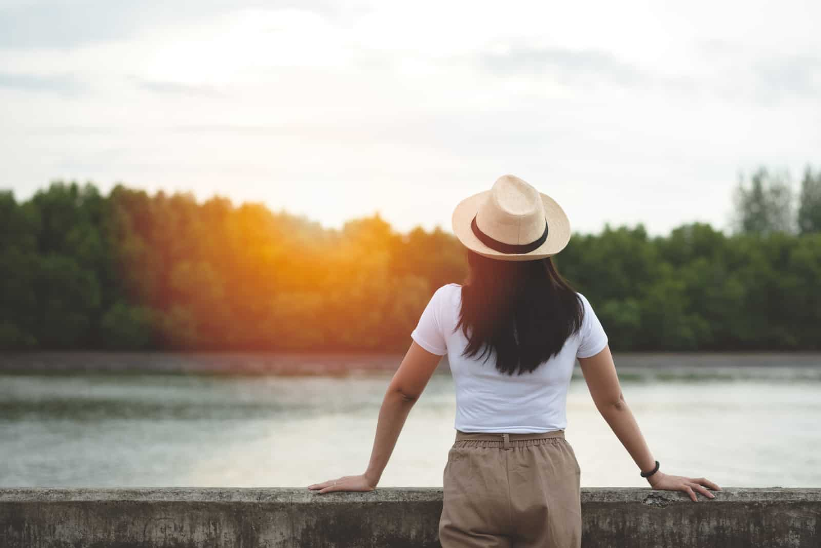 a black-haired woman with a hat on her head stands and looks at the river