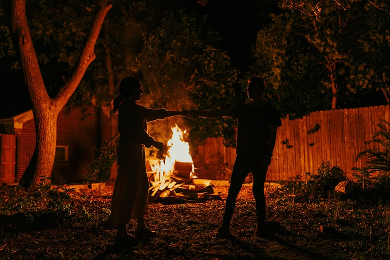 a couple dancing near the fire in the yard
