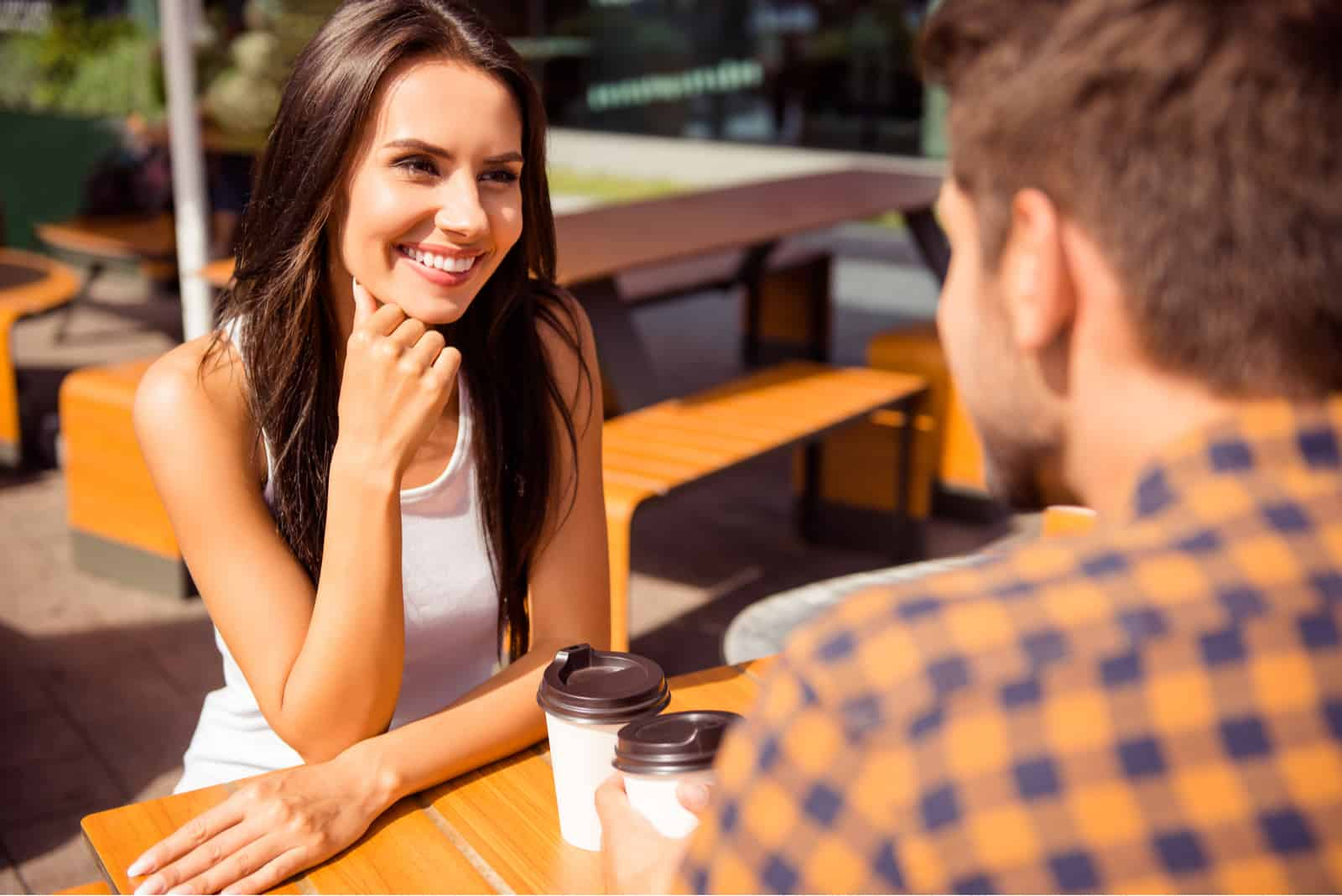 a couple in love sitting at a table outdoors and talking