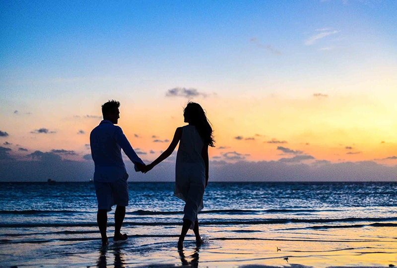 a couple walking on seashore while holding hands