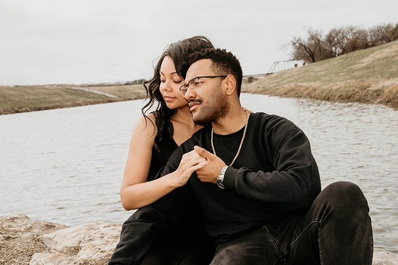 a loving couple holding hands sitting near the river