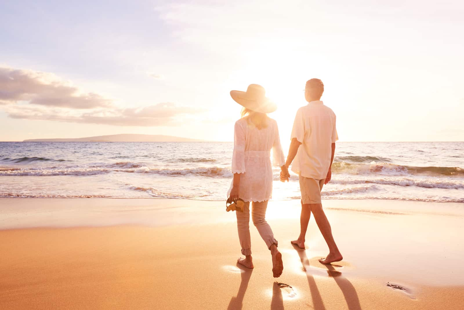 a man and a woman are walking along the beach