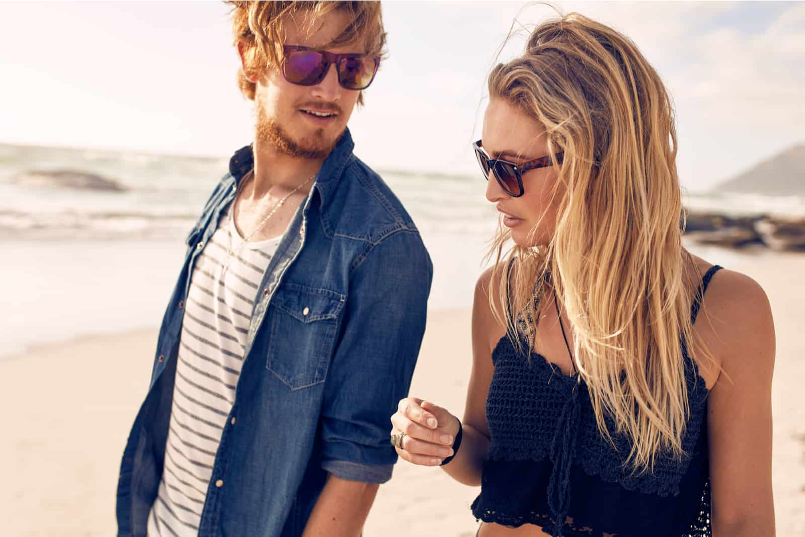 a man and a woman are walking along the beach and talking
