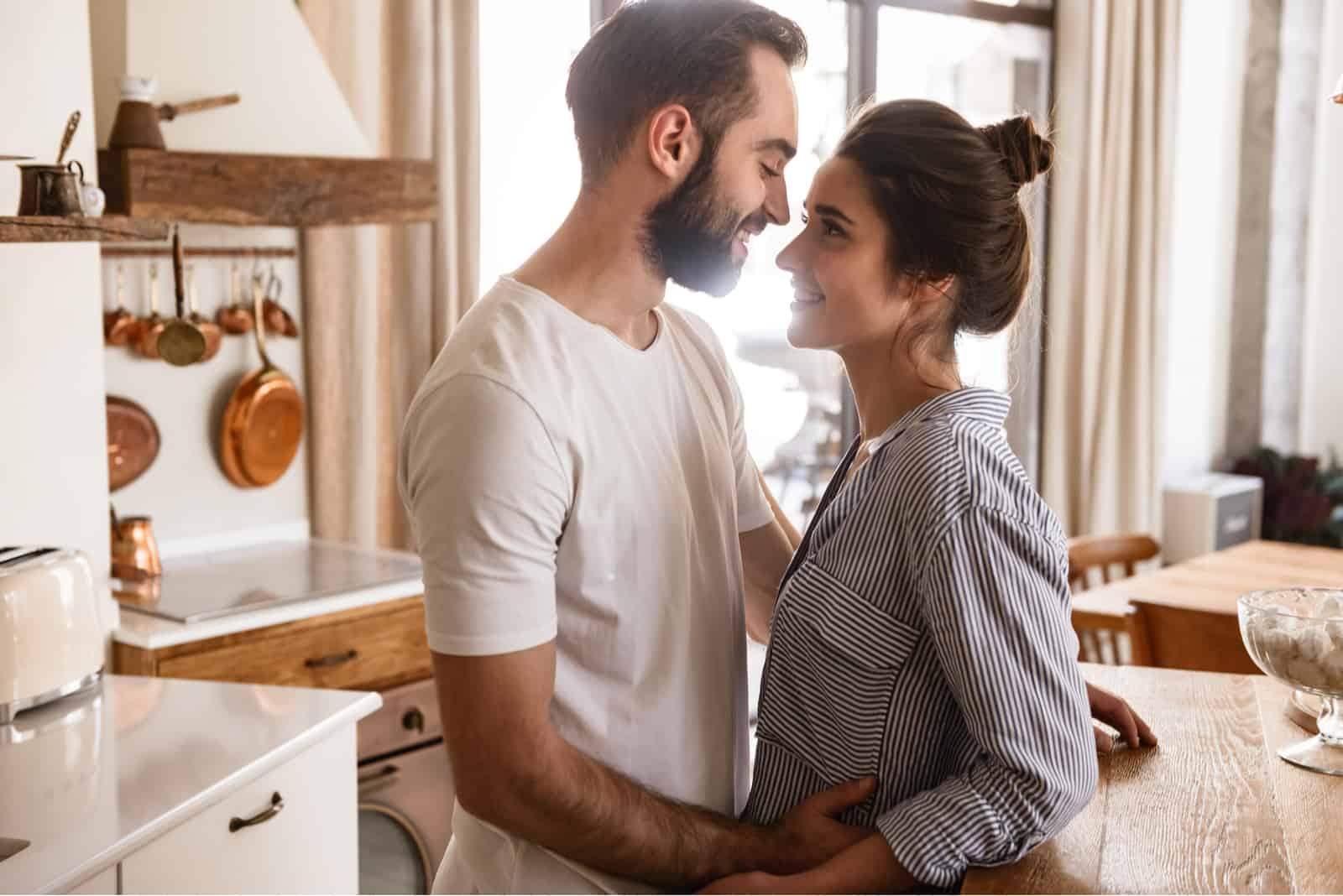 a man and a woman embracing in the kitchen